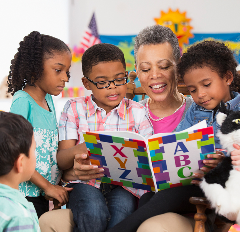 Caregiver reading to children at daycare.