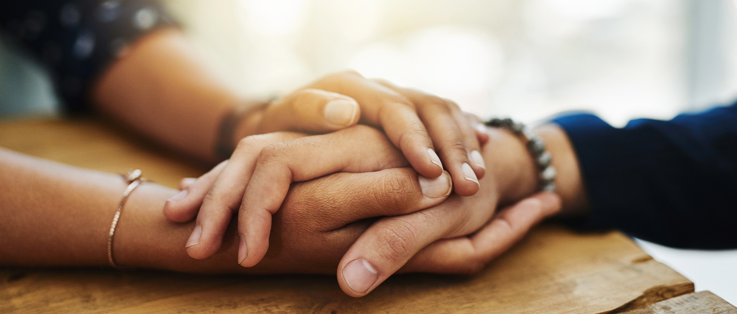 Image of two people holding hands to convey comfort and grief.
